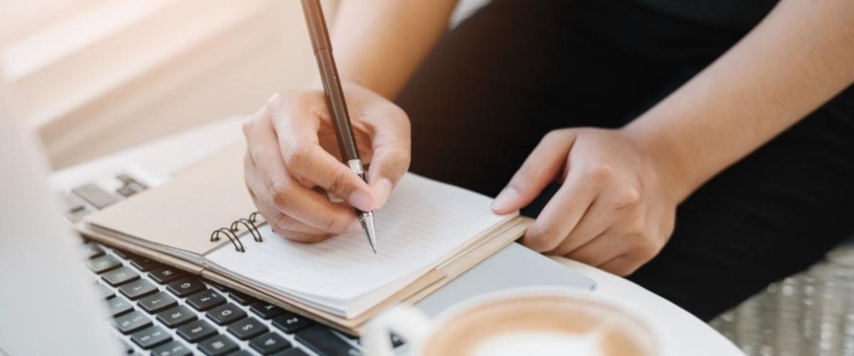 una mujer escribe en un libro